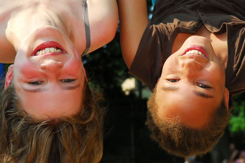 1237436 - two girls hanging upside down in a playground